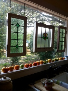 stained glass hangs in a kitchen window, ripe tomatoes line the sill